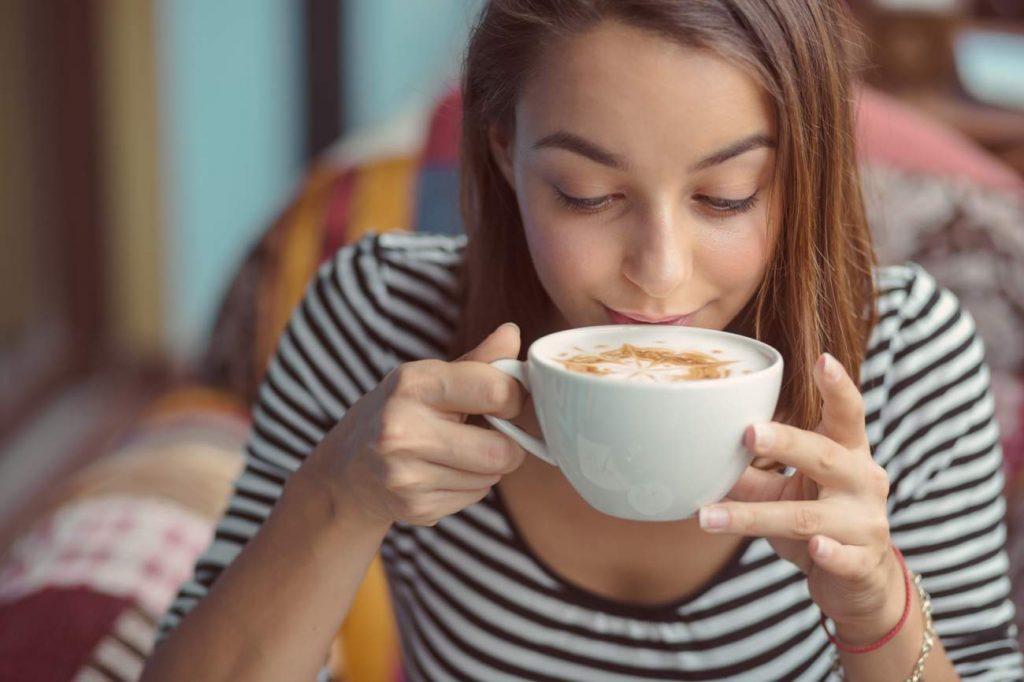 Junge Frau, Cappuccino, Kaffeegenuss, Lächeln, Gemütlichkeit, Geborgenheit, sich selbst Freude bereiten, Ideen sich eine Freude machen