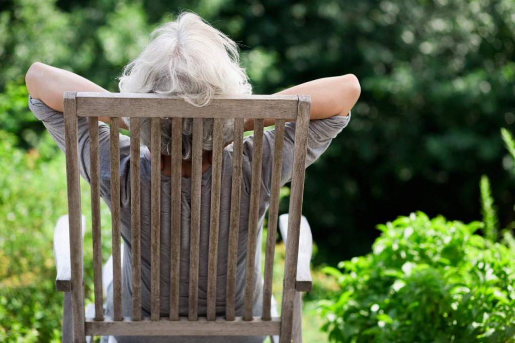 Frau, Holzstuhl, Schaukelstuhl, Entspannung, Sorglosigkeit, Freizeit, Sonne tanken, im Alter richtig abgesichert, sich für das Alter richtig abzusichern