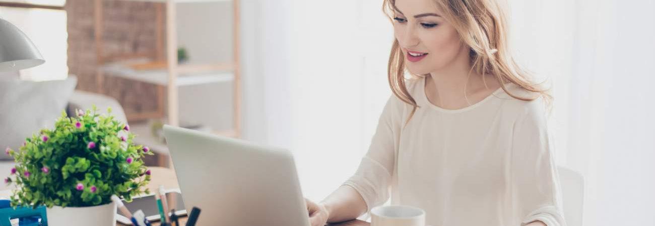 Frau, Laptop, Schreibtisch, Tasse, Stiftebox, ARbeitsplatz, Büroarbeit, Homeoffice, Ausgeglichenheit, mehr Zufriedenheit im Job