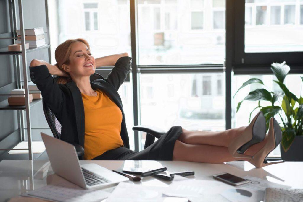 Frau, Schreibtisch, Zurücklehnen, Beine auf Tisch, Füße hochlegen, Laptop, Arbeitsplatz, Lächeln, Fenster, Büro, Tipps im Beruf erfolgreich
