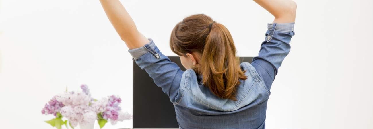 Frau, sich strecken, Schreibtisch, Bildschirm, Rücken, Verspannung, Arbeitsplatz, Bewegungstipps, Tipps für mehr Bewegung im Alltag