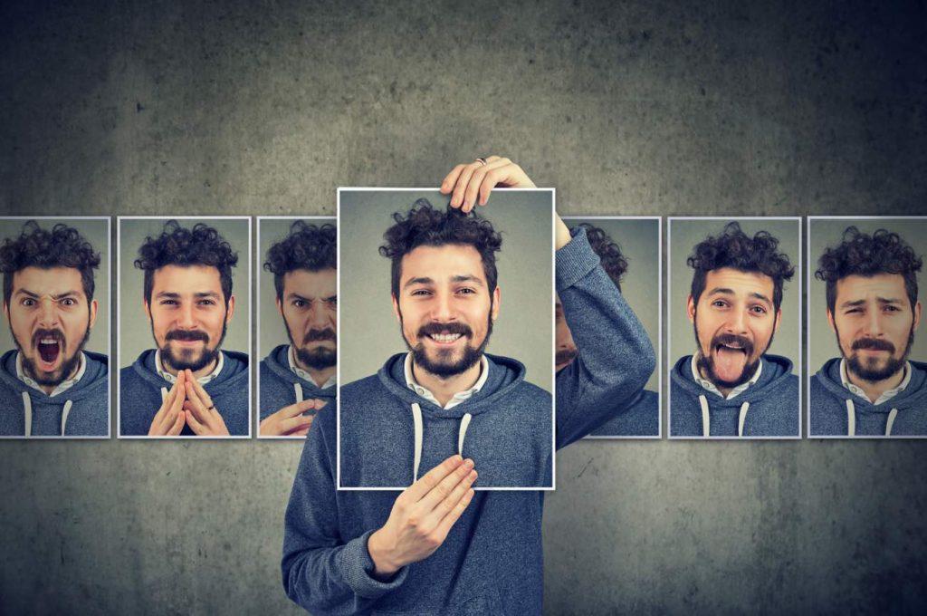 junger Mann, Locken, Bilder, Bilderrahmen, Emotionen, Reaktionen, grauer Hintergrund, Pullover, Vielfalt, Gefühlsspektrum, Abstufungen, eigene Persönlichkeit, persönliche Eigenschaften