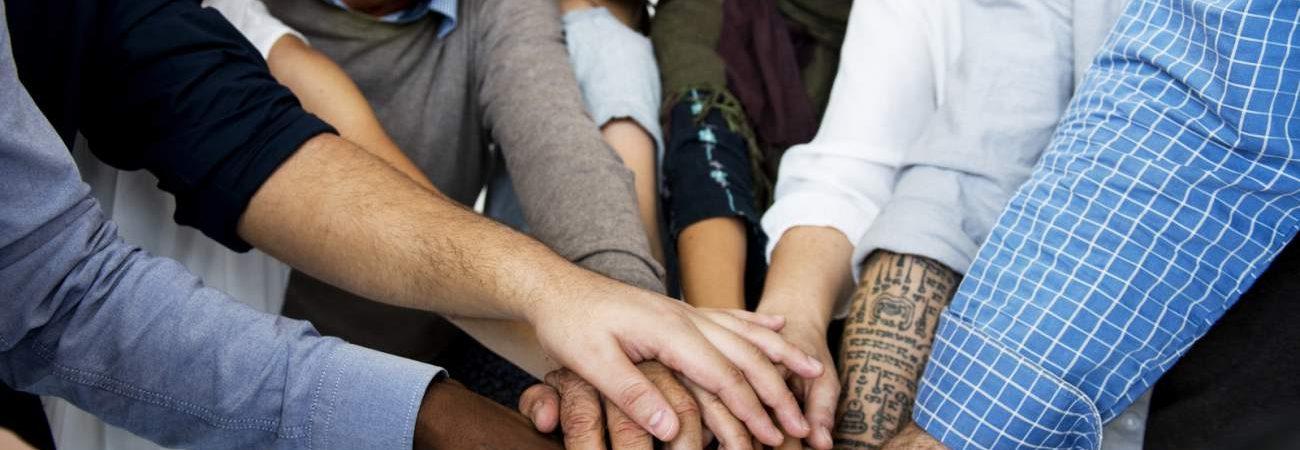 Menschen, Diversität, Gruppe, Hände, Zusammenhalt, Zusammenarbeit, Gemeinschaftsgefühl, gute Laune, Lächeln, soziales Engagement, sich sozial engagieren, ehrenamtliche Tätigkeiten, Tipps, Ideen, Vorteile