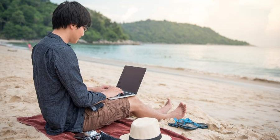 Junger Asiate sitzt auf einem Strandtuch am Strang mit dem Blick in Richtung Wasser, Laptop auf dem Schoß, neben sich Sonnenut und Digitalkamera